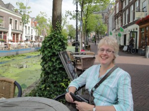Angie Macdonald sitting at a table beside a canal in Delft