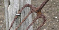 rusty garden pitchfork on wooden post