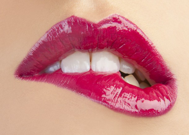 close-up of woman biting her pink lipsticked bottom lip