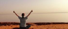 woman doing yoga breathing on beach