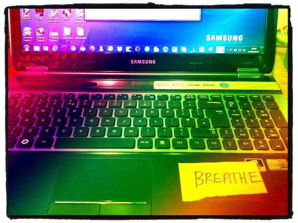 laptop computer with a note saying breathe on it