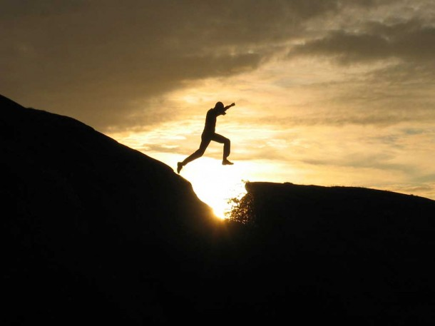 figure leaping across a ravine in the sunset