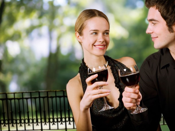 happy couple smiling at each other and holding glasses of red wine