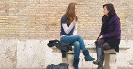 two women friends sitting on stone bench and talking