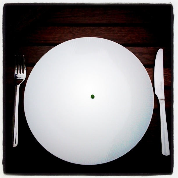 single pea in the middle of a white plate, knife and fork