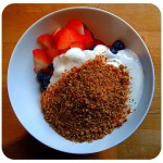 strawberries, blueberries, yoghurt and ground seeds in breakfast bowl