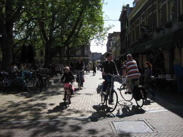 people riding bicycles through the streets of Delft