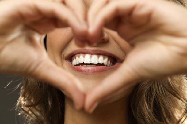 woman's smile and hands in a heart shape in front of face