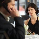 couple in restaurant, man having mobile phone conversation