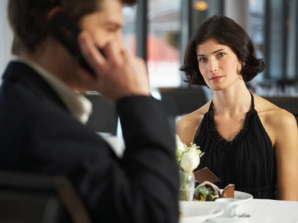 couple in restaurant, man having mobile phone conversation