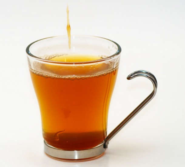 A cup of black tea with honey dripping into it