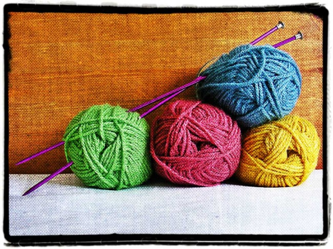 Coloured balls of wool and knitting needles to illustrate the health benefits of knitting