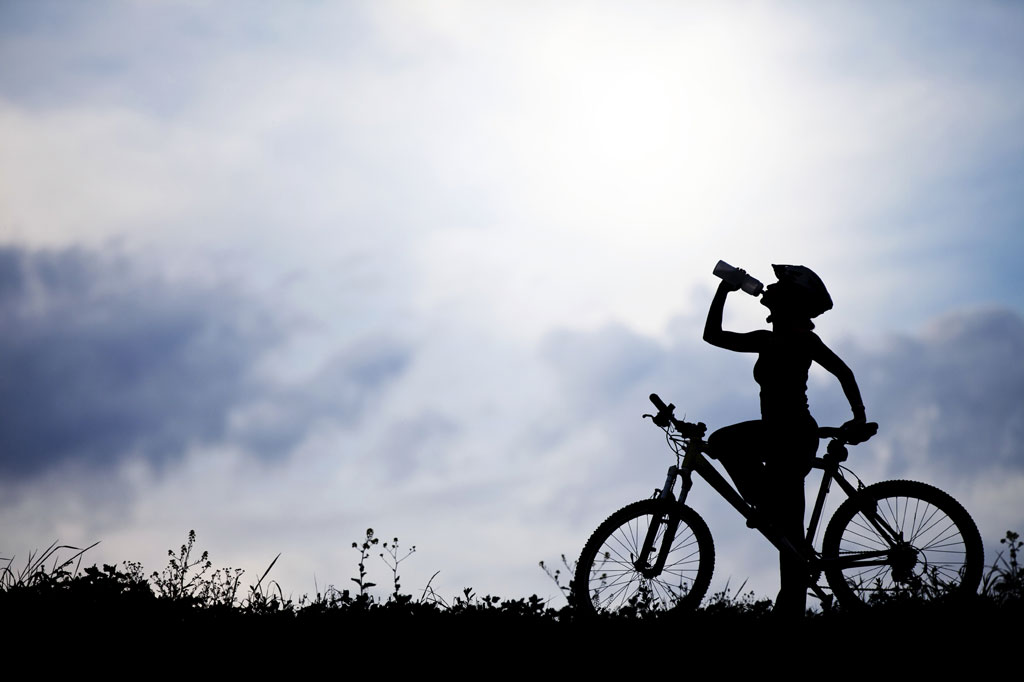 Female cyclist drinking water to demonstrate testosterone deficiency in women